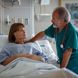 A doctor speaks with his patient at her bedside.