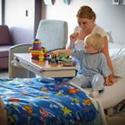 A female plays with a toddler at his hospital bed.