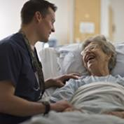 A nurse visits with an elderly female patient at her hospital bed.