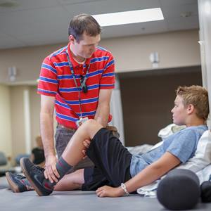 A physical therapist checks the leg or knee of his patient.