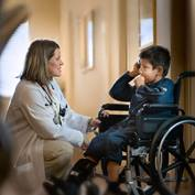 A female provider talks with a pediatric patient who is in a wheelchair.