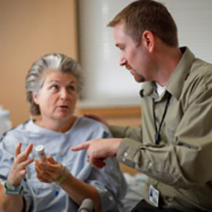 A doctor meets with one of his female patients to discuss a medication that he has prescribed for her.