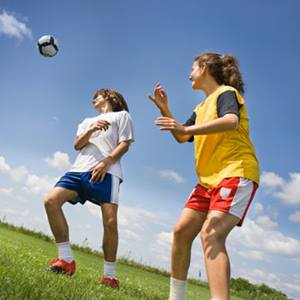 Two teens playing soccer