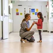 Intermountain Nurse kneeling by child