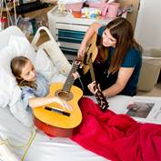 girl-and-female-volunteer-bed-playing-guitars