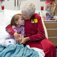 older-female-embracing-kissing-young-girl-patient