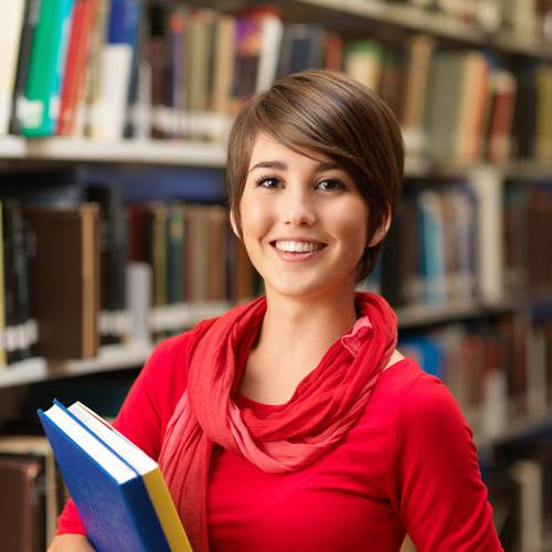 A female student in a library holding books