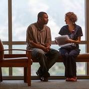 A nurse in blue scrubs holding papers in her hand talks with a male patient in a clinic waiting room