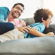 dad tickling kids on couch_square