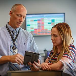 male-and-female-employees-looking-at-tablet