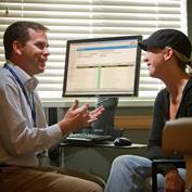 A male doctor sitting in front of a computer talks with a female patient wearing a black baseball cap