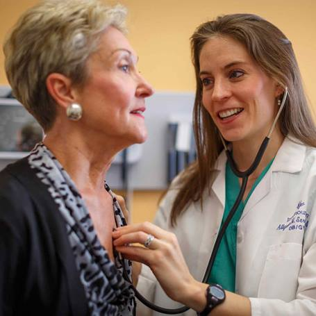 Young female physician checking the heartbeat of a older female patient in a clinic exam room