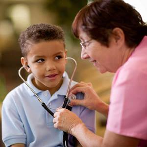 A female physician uses a stethoscope to show a male child his heartbeat