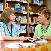 A female nurse and a female patient are reading a book together in a library
