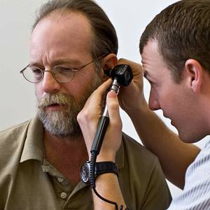 A male physician gives an ear exam to an older male patient