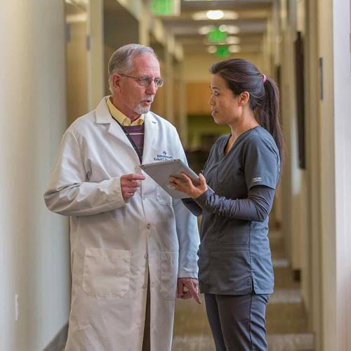 An older male doctor speaks with a younger female nurse holding a tablet in a clinic hallway