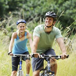 A man and woman in helmets are riding bicycles in the countryside.