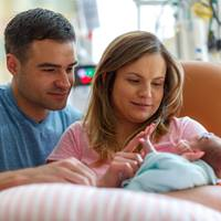 parents-hold-infant-in-nicu