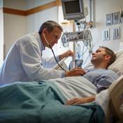 physician-examining-patient-hospital-bed