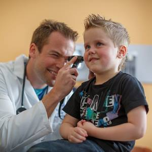 physician-looking-into-boys-ear