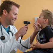physician-looking-into-boys-mouth