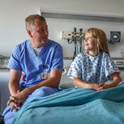 physician-talking-to-girl-hospital-bed