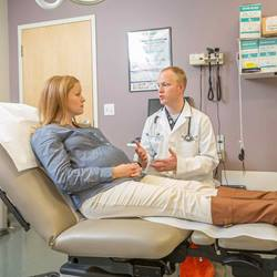 A male physician consults a pregnant patient sitting in an exam chair