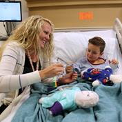 A child-life specialist helps a pediatric patient understand a procedure