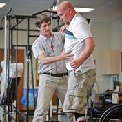 A physical therapist assists a patient during therapy