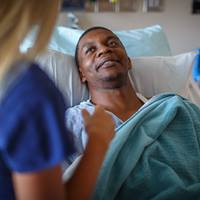 male-patient-hospital-bed-nurse-in-background
