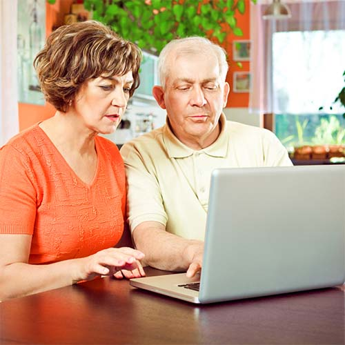 An older man and woman are sitting together at their computer