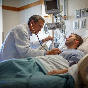 Patient In Hospital Pic : physician-examining-patient-hospital-bed